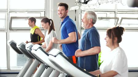 strong granny : Young and elderly people running on treadmill. Young handsome man runs on treadmill and looking at camera. Workout at modern fitness club.