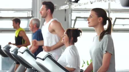 all ages : Group of people training on treadmill. Young woman exercising at gym. Sport for all ages. Stock Footage