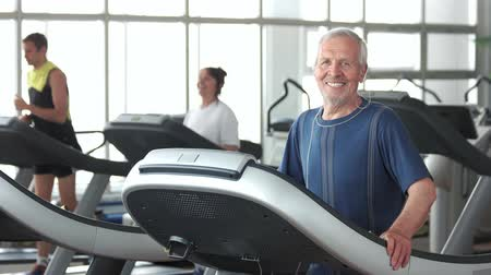 stay active : Smiling aged man exercising at gym. Senior man in sportswear running on treadmill and looking at camera. Stay active through your years. Stock Footage