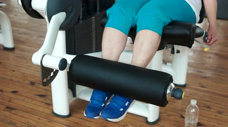quadriceps : Close up female legs on weight lifting machine. Elderly woman doing weight lifting exercise at gym. Stock Footage