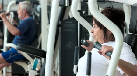 strong granny : Female pensioner training at gym, side view. Attractive senior woman working out at fitness center close up. Sport, wellness and healthcare.