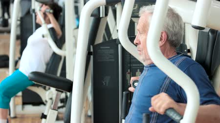 uzun ömürlü : Elderly male person training at gym. Senior man exercising on machine at fitness club, side view. Active way of life.