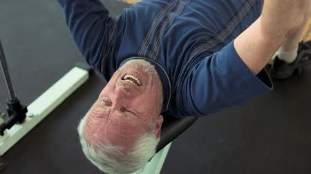 motivo : Senior man doing bench press exercise. Male pensioner lifting weight at gym close up. Reasons to strat lifting weights. Stock Footage