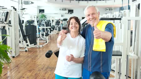 strong granny : Happy couple of seniors gesturing thumb up. Smiling elderly people showing thumb up at gym. Sport and seniors.