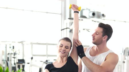 melegítőben : Woman doing exercises with dumbbell on a gym background. Pretty smiling girl training with dumbbell with a help of fitness trainer. Stock mozgókép