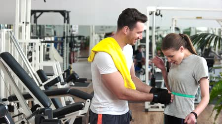 centímetro : Fitness trainer measuring waist of female client. Personal trainer measuring progress in training of client. Satisfied woman expressing her success at gym. Sport and diet concept.