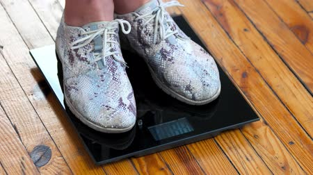 weighing machine : Close up female legs standing on scales. Female legs standing on black digital scales. Control of weight concept. Stock Footage