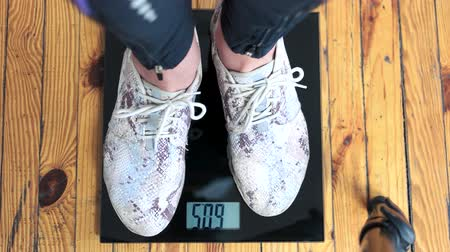 weighing machine : Female feet standing on weight scales. Woman legs standing on digital scales close up. Diet and weight loss concept.