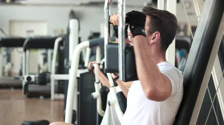 trener : Athletic gym trainer doing chest press exercise. Young handsome man using exercise equipment at gym. Wideo