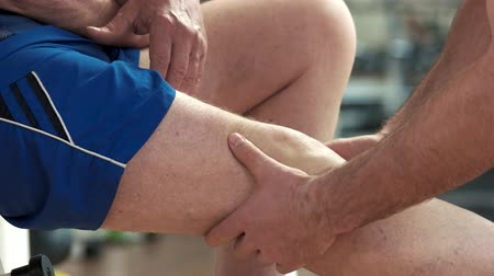 kaslı : Trainer massaging injured leg close up. Leg injury during fitness training. Stok Video