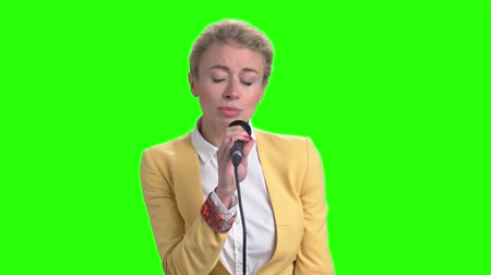 sostituzione : Young pretty blonde singing with microphone. Elegant girl holding microphone and singing on chroma key background. Beautiful caucasian singer.