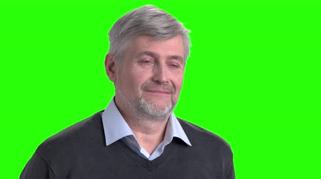 positief denken : Smiling mature man on green screen. Pensive middle-aged man is smiling on chroma key background. Good memories concept.