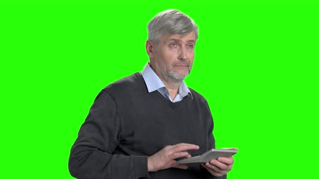 substituição : Senior man working on calculator. Mature man calculating finance on chroma key background close up.