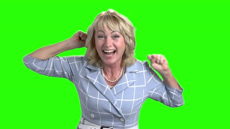 raising fist : Excited mature woman on green screen. Joyful woman raised hands in excitement on chroma key background. Middle-aged woman triumphing victory.