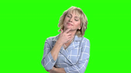 pszichológia : Relaxing woman on green screen background. Mature woman closed eyes and dreaming on chroma key background. Woman has a rest. Stock mozgókép