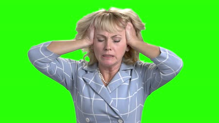 испуг : Desperate mature woman on chroma key background. Depressed anxious businesswoman pulling her hair on Alpha Channel background. Human expression of despair.