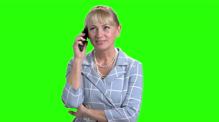 вырезка : Mature woman talking on mobile phone. Middle aged caucasian woman talking on smartphone on chroma key background.