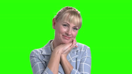 clasped : Portrait of gorgeous mature woman on green screen. Charming middle aged woman clasped her hands under chin on chroma key background. Feminine beauty and charm.