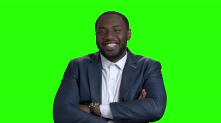 afroamerican : Smiling afro american manager on green screen. Successful afro american entrepreneur crossed arms on chroma key background. People and business concept. Stock Footage