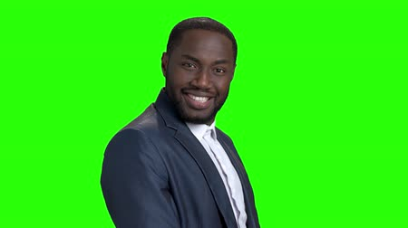 вырезка : Young sexy stylish businessman on green screen. Smiling self-assertive dark-skinned businessman on Alpha Channel background. Стоковые видеозаписи