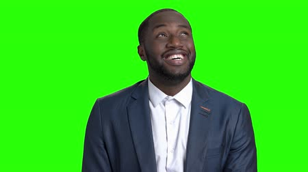 gözlem : Happy businessman is looking around on green screen. Happy confused afro-american man in business suit on Alpha Channel background. Stok Video