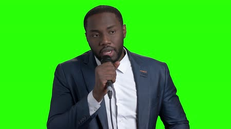 dark skinned : Afro-american entertainer talking on green screen. Dark-skinned man in elegant suit talking into microphone on chroma key background.