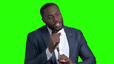вырезка : Afro-american tv presenter on green screen. Attractive dark-skinned entertainer talking into microphone on Alpha Channel background. Стоковые видеозаписи