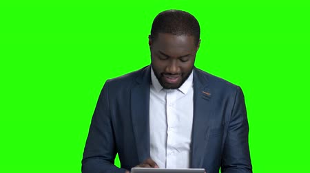 dark skinned : Smiling entrepreneur using digital tablet. Cheerful afro-american businessman working on pc tablet and looking at camera on chroma key background.