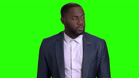 punctuality : Attractive businessman waiting for someone. Serious afro american business person standing and looking aside with anticipation on green screen.