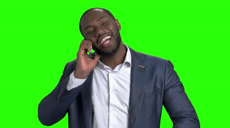 точность : Cheerful dark-skinned manager talking on phone. Smiling entrepreneur talking on phone and checking time on wristwatch on green screen. Young afro-american businessman is in a hurry for meeting. Стоковые видеозаписи