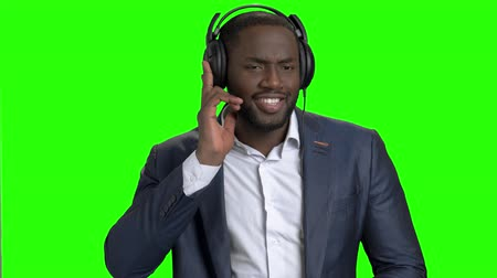 substituição : Stylish businessman listening to music in headphones. Portrait of cheerful afro american entrepreneur singing and dancing on Alpha Channel background.