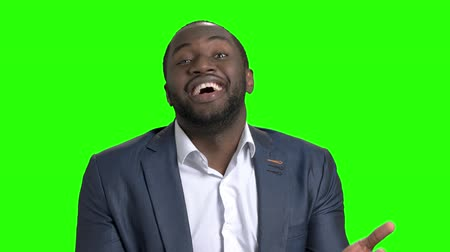 босс : Afro-american businessman is expecting for a right answer. Man in formal wear with hands on belt looking at camera on green screen. Man disappointed with answer. Discrepancy with expectation.