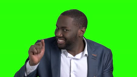 dedo humano : Playful dark-skinned businessman on green screen. Young cheerful afro-american man in formal wear inviting you to dance on chroma key background. Lets dance concept. Stock Footage