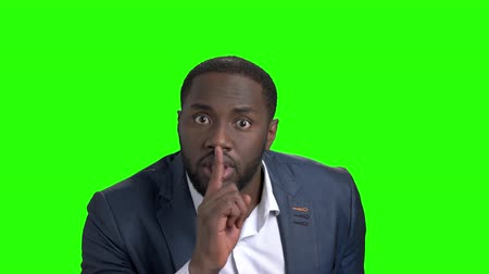 substituição : Afro-american businessman showing silence gesture. Portrait of young serious businessman placing finger on lips saying shhh, be quiet on chroma key background. Human body language.
