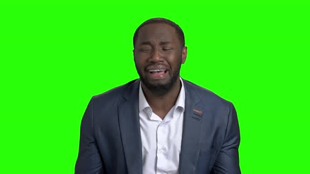 fatality : Desperate businessman crying on green screen. Afro american man in business suit in full despair on Alpha Channel background. Stock Footage