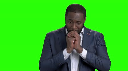 repentance : Portrait of businessman regretting about something. Unhappy afro american entrepreneur with clasped hands on chroma key background. Stock Footage