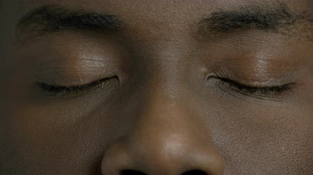 avelã : Close up dark-skinned man closed eyes. Afro-american male person is openes his eyes close up. Black man eyes. Stock Footage