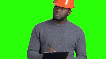 darkskinned : Confident engineer making a note on clipboard. Afro american foreman in hard hat writing on clipboard on chroma key background. Checking new object.