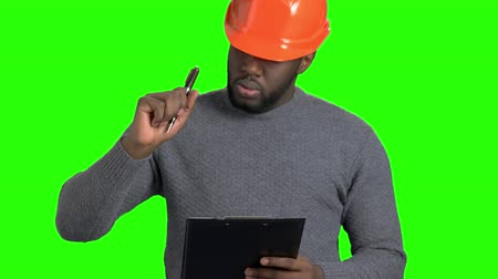 darkskinned : Male engineer checking new object. Afro american supervisor in hard hat making a note on clipboard on Alpha Channel background.