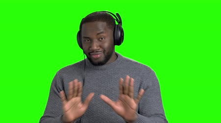 darkskinned : Afro american guy is dancing on green screen. Portrait of handsome dark-skinned man with headphones dancing on chroma key background.