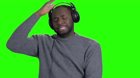 darkskinned : Man in headphones is dancing on green screen. Cheerful energetic african-american guy is listening to music, dancing and showing thumbs up on chroma key background. Stock Footage