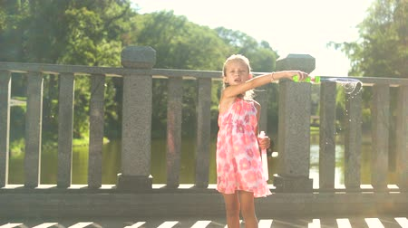 hůlky : Child with bubble blower outdoors. Cute little girl in dress blowing soap bubbles on bridge. Summer vacation concept.