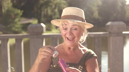 paz mental : Happy senior woman with bubble blower. Cheerful elderly woman having fun blowing soap bubbles outdoors.