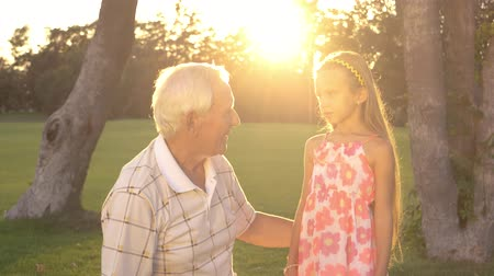 bilge : Girl with grandpa outdoors. Senior man having a conversation with his granddaughter in park. Wisdom, mind and experience of elderly generation.
