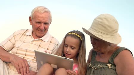 возможность : Girl with seniors using pc tablet. Caucasian little girl with gadget outdoors. The possibilities of modern technologies make life easier. Entertainment with gadget on summer nature.