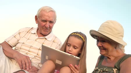 dojem : Granddaughter with pc tablet and surprised grandmother. Senior people with grandchild outdoors. Modern technology and skills of kids.