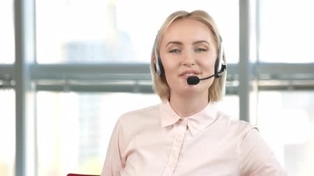 keyifli : Mature female employee is working in call center. Portrait of smiling woman with microphone is talking.
