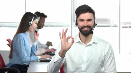 operators : Young brutal man in office showing ok gesture. Smiling male with beard in office workers background with bright room.