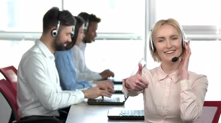 оператор : Cheerful blond lady in office showing thumb up. Woman in call center office showing her approval. Стоковые видеозаписи