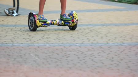 gyro : 17.09.2017 - Kyiv, Ukraine. Riding gyroscooter on cobblestone surface. Legs on youth trendy colourful gyroboard.